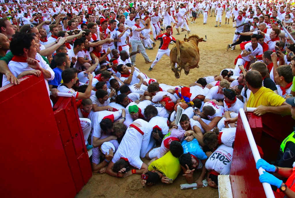 A fighting cow leaps over revellers upon entering the bullring following the first running of the bulls of the San Fermin festival in Pamplona